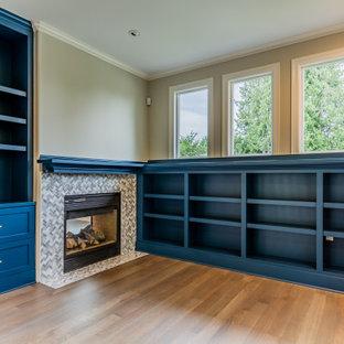 Modelo de despacho actual con paredes beige, suelo de madera en tonos medios, chimenea tradicional, marco de chimenea de baldosas y/o azulejos y suelo marrón