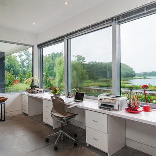 Cette photo montre un grand bureau moderne de type studio avec un mur blanc, béton au sol, un bureau indépendant et un sol gris.