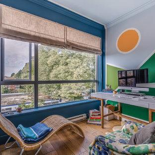 Foto di un atelier bohémian di medie dimensioni con pareti multicolore, pavimento in legno massello medio, nessun camino, scrivania autoportante e pavimento marrone