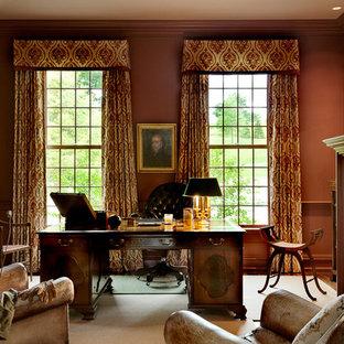 Ispirazione per uno studio classico con pareti rosse, camino classico, cornice del camino in pietra e scrivania autoportante