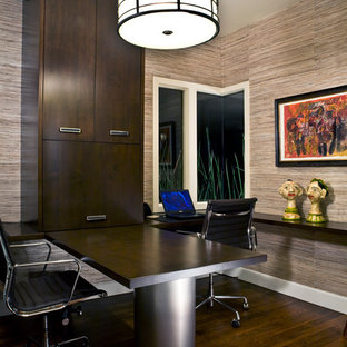 Example of a trendy built-in desk dark wood floor home office design in Phoenix with beige walls and no fireplace