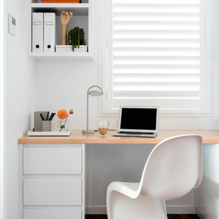Photo of a beach style home office in Brisbane with white walls, dark hardwood floors, a built-in desk and brown floor.