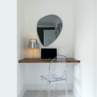 This is an example of a small contemporary study in Essex with white walls, carpet, a built-in desk and grey floors.