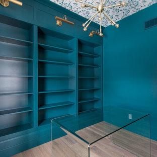 トロントの中くらいのコンテンポラリースタイルのおしゃれなホームオフィス・書斎 (無垢フローリング、青い壁、暖炉なし、自立型机、茶色い床) の写真