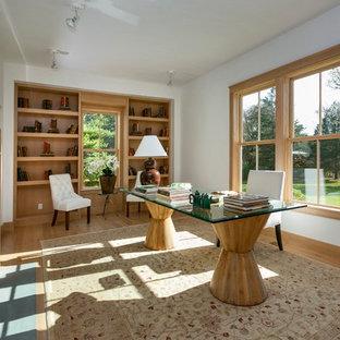 Mittelgroßes Modernes Arbeitszimmer mit Kaminumrandung aus Beton, Arbeitsplatz, weißer Wandfarbe, hellem Holzboden, Kamin und freistehendem Schreibtisch in New York