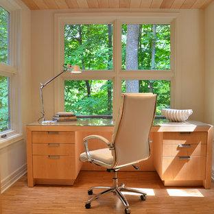 Foto de despacho actual con paredes beige, suelo de madera en tonos medios y escritorio independiente