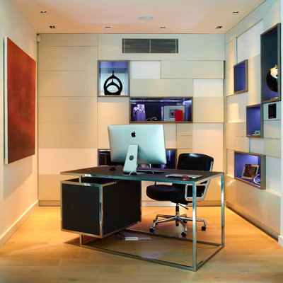 Example of a mid-sized trendy freestanding desk light wood floor study room design in London with beige walls