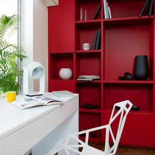 Immagine di uno studio contemporaneo con pareti rosse, parquet scuro e scrivania autoportante