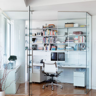 Modelo de despacho actual con paredes blancas, suelo de madera en tonos medios y escritorio empotrado