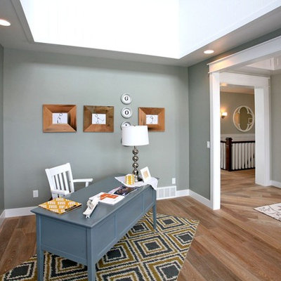 Example of a large trendy freestanding desk medium tone wood floor and brown floor study room design in Salt Lake City with gray walls and no fireplace