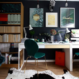 This is an example of a bohemian study in Surrey with a freestanding desk, brown floors, black walls and medium hardwood flooring.