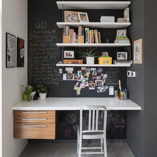 Cette image montre un bureau design avec un mur noir, aucune cheminée, un bureau intégré et un sol gris.
