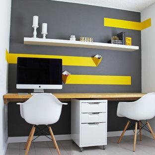 Идея дизайна: маленький кабинет в современном стиле с разноцветными стенами, деревянным полом, встроенным рабочим столом и серым полом