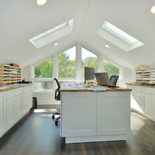 Large transitional built-in desk dark wood floor home studio photo in Chicago with white walls
