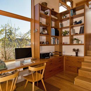 Réalisation d'un bureau design de taille moyenne avec un mur blanc, un sol en bois brun, aucune cheminée et un bureau intégré.