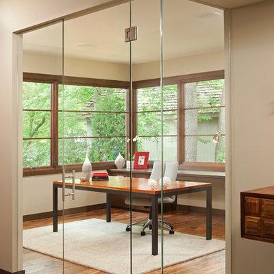 Example of a trendy freestanding desk dark wood floor home office design in Minneapolis with beige walls
