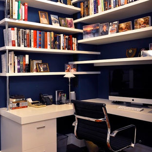 Home office - small contemporary built-in desk dark wood floor and brown floor home office idea in New York with blue walls