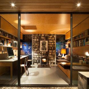 Imagen de estudio madera y panelado, actual, pequeño, panelado, con paredes amarillas, suelo de madera pintada, estufa de leña, marco de chimenea de metal, escritorio empotrado, suelo gris y panelado