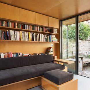 This is an example of a small contemporary home studio in London with yellow walls, painted wood flooring, a wood burning stove, a metal fireplace surround, a built-in desk, grey floors, a wood ceiling and panelled walls.