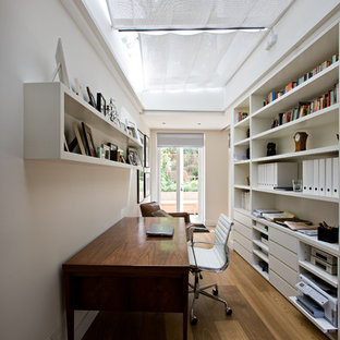 Example of a trendy freestanding desk medium tone wood floor home office design in London with white walls