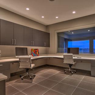 Foto på ett mycket stort funkis arbetsrum, med grå väggar och ett inbyggt skrivbord