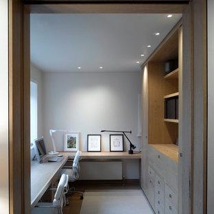 Inredning av ett modernt arbetsrum, med vita väggar och mörkt trägolv