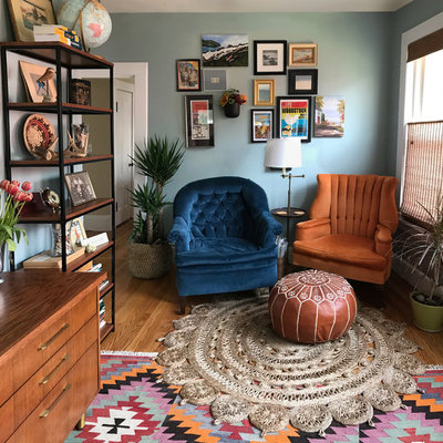 Mid-sized eclectic medium tone wood floor and brown floor home office library photo in Boston with blue walls