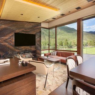 Exemple d'un très grand bureau tendance avec un mur beige, un sol en bois brun, une cheminée ribbon, un manteau de cheminée en pierre et un bureau indépendant.