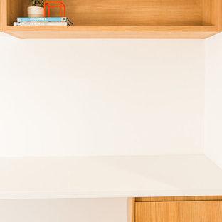 Immagine di uno studio design con pareti bianche, moquette, scrivania incassata e pavimento grigio