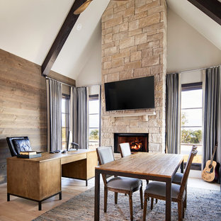 Klassisches Arbeitszimmer mit Arbeitsplatz, weißer Wandfarbe, hellem Holzboden, Kamin, Kaminumrandung aus Stein, freistehendem Schreibtisch und beigem Boden in Sonstige