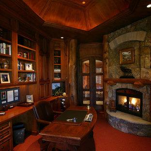 Diseño de despacho rural, grande, con moqueta, chimenea de esquina, marco de chimenea de piedra, escritorio independiente y suelo rojo