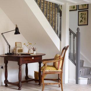 Modelo de despacho campestre, pequeño, sin chimenea, con paredes blancas, suelo de piedra caliza, escritorio independiente y suelo beige
