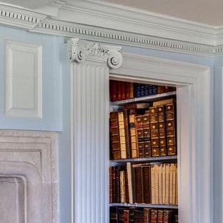 Idee per uno studio american style con libreria, pareti blu, camino classico e cornice del camino in pietra