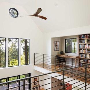 Diseño de despacho contemporáneo, de tamaño medio, sin chimenea, con paredes blancas, suelo de madera en tonos medios y escritorio empotrado