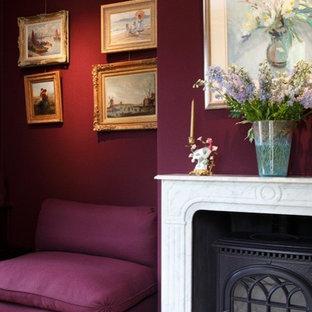 ロンドンの中サイズのカントリー風おしゃれなクラフトルーム (紫の壁、カーペット敷き、薪ストーブ、石材の暖炉まわり、ベージュの床) の写真