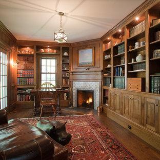 Идея дизайна: большое рабочее место в классическом стиле с коричневыми стенами, темным паркетным полом, угловым камином, фасадом камина из плитки и отдельно стоящим рабочим столом