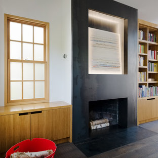 Inspiration for a contemporary home office and library in San Francisco with a reading nook, white walls, dark hardwood flooring, a standard fireplace, a metal fireplace surround, a freestanding desk and black floors.