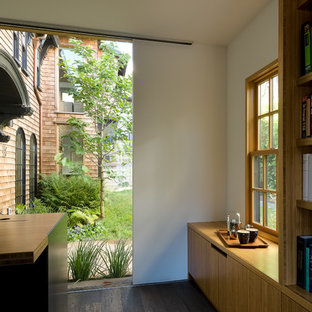 Contemporary home office and library in San Francisco with a reading nook, white walls, dark hardwood flooring, a standard fireplace, a metal fireplace surround, a freestanding desk and black floors.