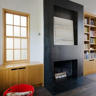 サンフランシスコのコンテンポラリースタイルのおしゃれなホームオフィス・書斎 (ライブラリー、白い壁、濃色無垢フローリング、標準型暖炉、金属の暖炉まわり、自立型机、黒い床) の写真