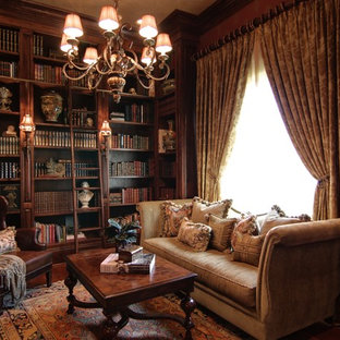 Mid-sized ornate freestanding desk dark wood floor home office library photo in New Orleans with brown walls