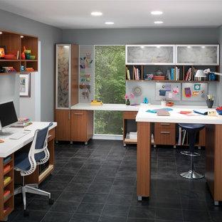 Diseño de sala de manualidades minimalista, grande, sin chimenea, con escritorio empotrado, paredes grises y suelo de baldosas de cerámica