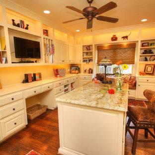 Mittelgroßes Klassisches Nähzimmer ohne Kamin mit gelber Wandfarbe, braunem Holzboden und Einbau-Schreibtisch in Dallas