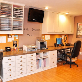 Esempio di una stanza da lavoro di medie dimensioni con pareti arancioni, pavimento in legno massello medio e scrivania incassata