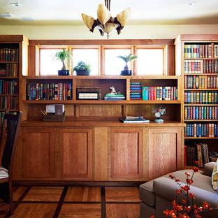 Immagine di un ufficio stile americano di medie dimensioni con pareti gialle, pavimento in legno massello medio, nessun camino e scrivania incassata