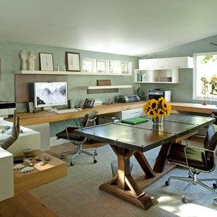 ニューヨークの広いトランジショナルスタイルのおしゃれなホームオフィス・書斎 (青い壁、無垢フローリング、造り付け机、暖炉なし) の写真