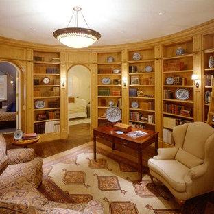 Diseño de despacho clásico, de tamaño medio, con paredes marrones, suelo de madera en tonos medios y escritorio independiente
