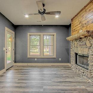 Ispirazione per uno studio american style di medie dimensioni con pareti nere, pavimento in vinile, camino bifacciale, cornice del camino in pietra e pavimento marrone