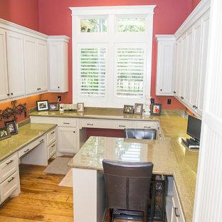 Großes Uriges Nähzimmer mit roter Wandfarbe, braunem Holzboden und Einbau-Schreibtisch in Houston