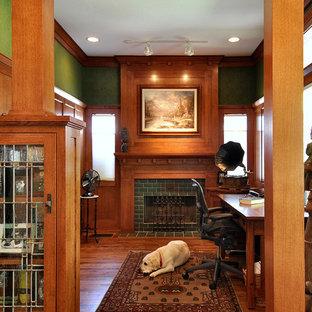Immagine di uno studio stile americano con pareti verdi, cornice del camino piastrellata e camino classico