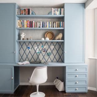 Inspiration för mellanstora klassiska hemmabibliotek, med beige väggar, mörkt trägolv, ett inbyggt skrivbord och brunt golv